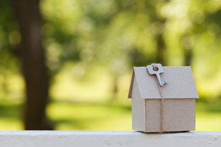 building loan: Model of cardboard house with key against natural green bokeh background. Building, loan, housewarming, insurance, real estate or buying a new home concept. Outdoor.