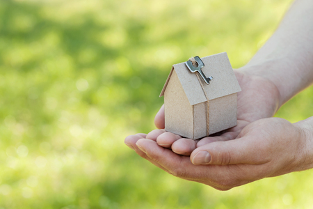 housewarming: Male hands hold of cardboard house with key against natural green bokeh background. Building, loan, housewarming, insurance, real estate or buying a new home concept. Outdoor. Stock Photo