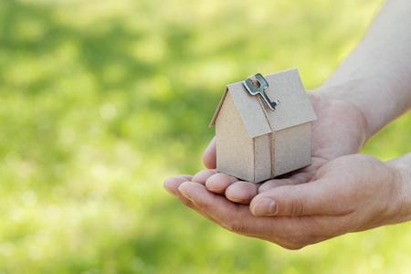 Mužské ruce drží kartonový dům s klíčem proti přírodnímu pozadí zeleného bokehu. Budování, půjčky, domácnosti, pojištění, nemovitosti nebo nákup nové koncepce domů. Venkovní.