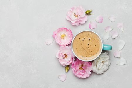 De ochtendkop van koffie en een mooie rozenbloemen op lichte achtergrond, hoogste mening. Gezellig ontbijt. Vlakke lay-stijl. Stockfoto