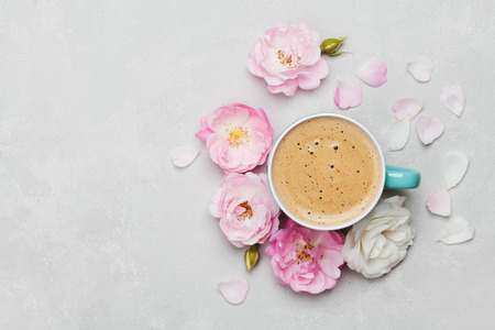 Morning Cup of coffee and a beautiful roses flowers on light background, top view. Cozy Breakfast. Flat lay style.