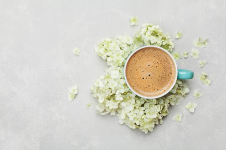Coupe matinale de café et une belle fleurs d'hydrangea sur fond clair, vue de dessus. Petit-déjeuner chaleureux. Style plat plat.