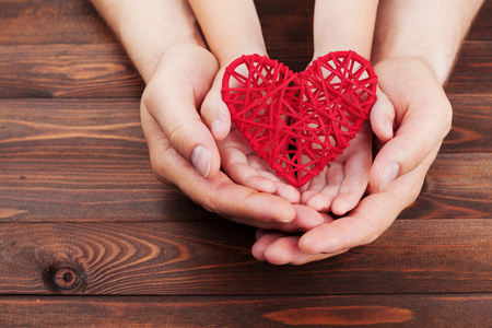 family relationships: Adult and child holding red heart in hands over a wooden table. Family relationships, health care, pediatric cardiology concept. Stock Photo