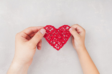 family relationships: Adult and child holding red heart in hands from above. Family relationships, health care, pediatric cardiology concept. Stock Photo