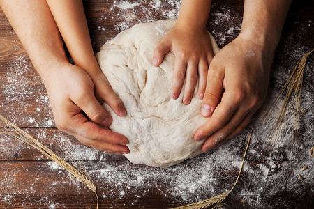 Father and child hands prepares the dough with flour, rolling pin and wheat ears on rustic wooden table from above. Homemade pastry for bread or pizza. Bakery background. Archivio Fotografico