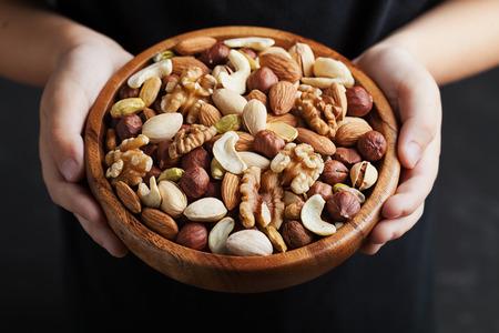De handen die van kinderen een houten kom met gemengde noten houden. Gezond eten en een snack. Walnoot, pistachenoten, amandelen, hazelnoten en cashewnoten. Stockfoto