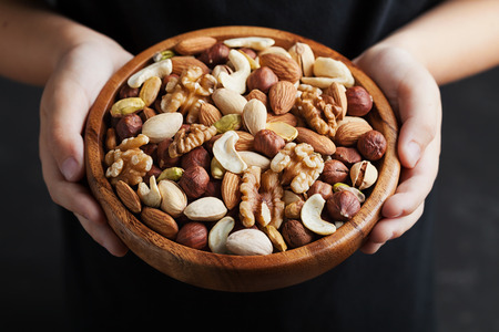 Childrens hands holding a wooden bowl with mixed nuts. Healthy food and snack. Walnut, pistachios, almonds, hazelnuts and cashews.