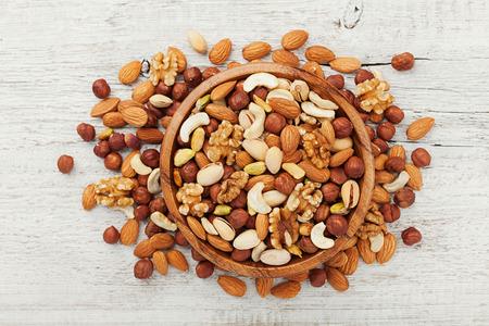 botanas: Tazón de madera con nueces mixtas en la vista superior de la tabla blanca. Comida sana y merienda. Nueces, pistachos, almendras, avellanas y anacardos.