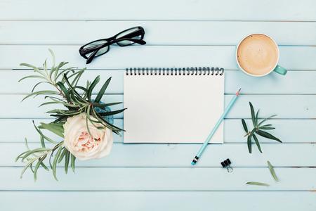 'S ochtends kopje koffie, schoon notebook, potlood, brillen en vintage rose bloem in de vaas op blauwe rustieke bureau bovenaanzicht. Planning en design concept. Gezellig ontbijt. Plat styling.