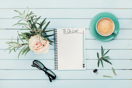 Morning coffee cup, notebook with to do list, pencil, eyeglasses and vintage rose flower in vase on blue rustic table from above. Planning and design concept. Cozy breakfast. Flat lay styling. Stock Photo