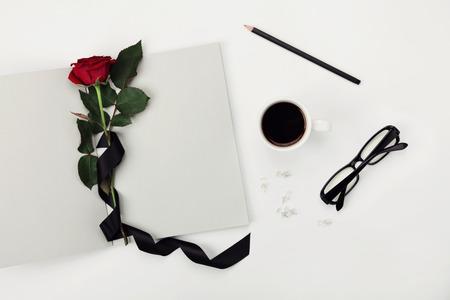 ruban noir: Womens espace de travail avec tasse de café, crayon, ordinateur portable vide, lunettes, ruban noir et de rose fleur sur blanc Vue de dessus de table. Appartement style laïque. Banque d'images