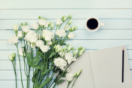 pencil and paper: Morning coffee cup, empty paper list, pencil, and bouquet of white flowers eustoma on blue rustic table overhead view. Woman working desk. Cozy breakfast. Flat lay styling.