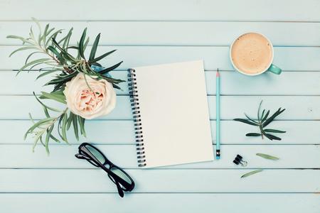 Mattina tazza di caffè, notebook pulito, matita, occhiali da vista e d'epoca rosa fiori in vaso sul blu tavolo rustico vista dall'alto. Progettazione e design concept. prima colazione accogliente. styling disteso.