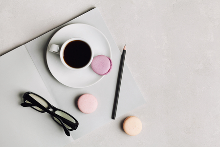 breakfast cup: Morning cup of coffee, empty notebook, pencil, glasses and cake macaron on gray desk overhead view. Beautiful breakfast. Flat lay.