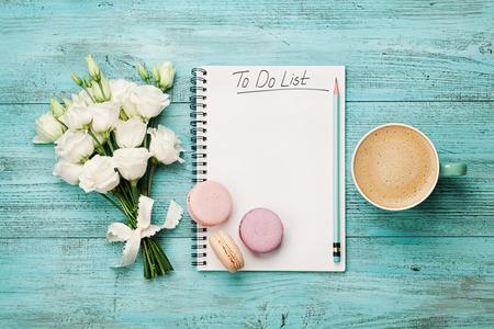 Koffie mok met macaron, witte bloemen en notitieboekje met omlijsting op blauwe rustieke tafel van bovenaf. Prachtig ontbijt. Vlak liggen. Stockfoto