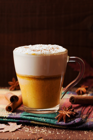 spiced: Pumpkin spiced latte or coffee in a glass on a wooden table. Autumn or winter hot drink.