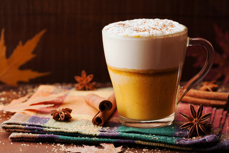 spiced: Pumpkin spiced latte or coffee in a glass on a rustic table. Autumn or winter hot drink. Stock Photo