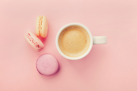 Cup of coffee with macaron on pink background from above, flat lay Foto de archivo