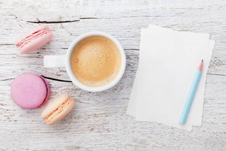 Cup of coffee with macaron and blank sheets on white wooden table from above, flat lay