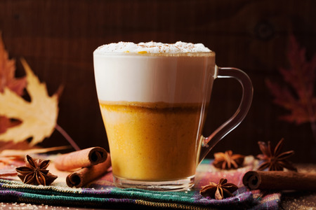 Pumpkin spiced latte or coffee in a glass on a wooden vintage table. Autumn or winter hot drink. Stock Photo