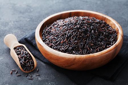 El arroz negro en un tazón de madera sobre una mesa oscura Foto de archivo - 63907707