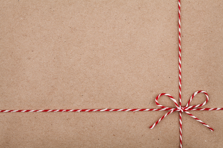 red paper: Christmas string or twine tied in a bow on kraft paper backdrop