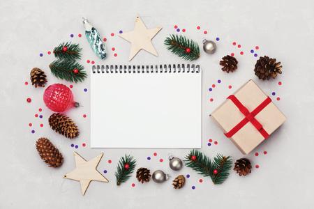Kerst achtergrond van de notebook, geschenkdoos, spar, kegelvrucht en vakantie decoraties op witte tafel van boven. Plat styling. Stockfoto