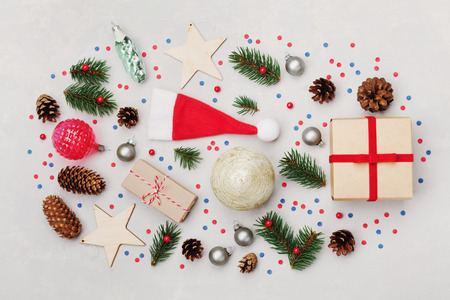 Christmas background of gift box, fir tree, conifer cone and holiday decorations on white desk top view. Flat lay styling. Stock Photo - 63907765