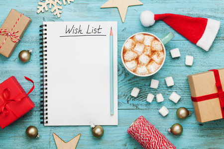 Cup of hot cocoa or chocolate with marshmallow, holiday decorations and notebook with wish list on turquoise vintage table from above, christmas planning concept. Flat lay style. Stockfoto