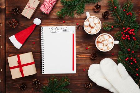 Twee kopjes hete cacao of chocolade met marshmallow, geschenken, wanten, Kerstmisspar en notebook met to do list op houten rustieke achtergrond van boven. Flat lay-stijl.