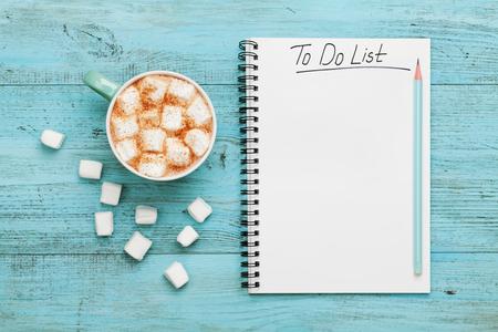 Kop warme chocolademelk of chocolade met marshmallow en notebook met to do list op turquoise vintage tafel van boven, kerst planning concept. Plat stijl. Stockfoto