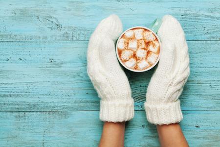 Frau, die Hände in den Handschuhen halten Tasse heißen Kakao oder Schokolade mit Marshmallows auf Türkis Jahrgang Tabelle von oben. Wohnung lag Stil.