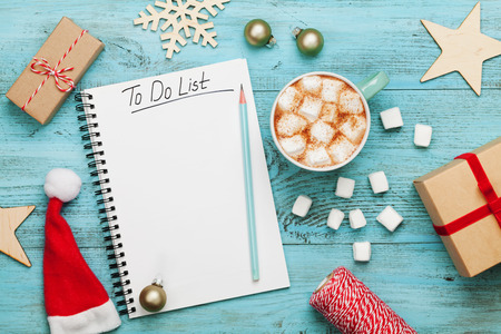 Cup of hot cocoa or chocolate with marshmallow, holiday decorations and notebook with to do list on turquoise vintage table from above, christmas planning concept. Flat lay style.
