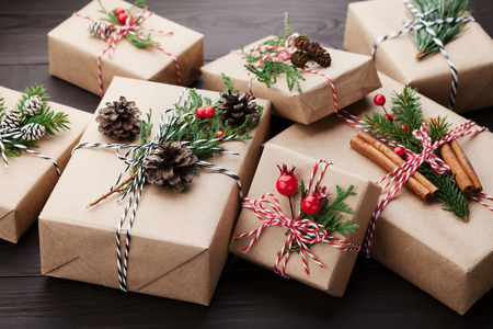 christmas present box: Heap of gift or present box wrapped in kraft paper with christmas decoration on rustic wooden background. Stock Photo
