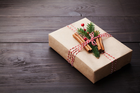 christmas present box: Gift or present box wrapped in kraft paper with christmas decoration on vintage wooden table. Copy space for text.