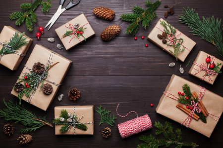 Gift or present box wrapped in kraft paper with christmas decoration on rustic wooden background from above. Flat lay style.
