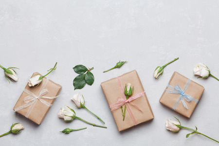 Gift or present box wrapped in kraft paper and rose flower on gray table top view. Flat lay styling. Copy space for text.
