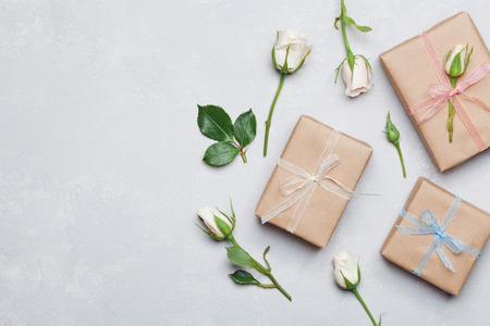 Gift or present box wrapped in kraft paper and rose flower on gray table from above. Flat lay styling. Copy space for text. 免版税图像