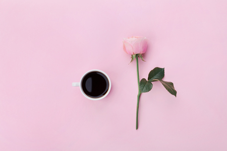 Pink rose flower and cup of coffee on pastel background top view. Flat lay style. Standard-Bild