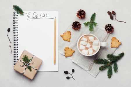 熱いココアやチョコレートとマシュマロ、クッキー、クリスマスの上から白いテーブルにリストを行うにノートブックのカップ。伝統的な冬の飲み物。フラットが横たわっていた。 写真素材 - 68961362
