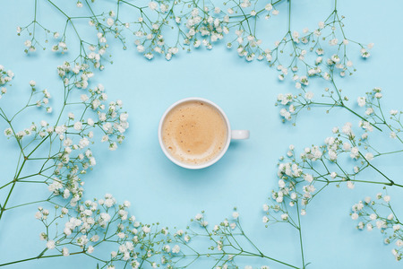 Morning cup of coffee and flower gypsophila on blue table from above. Cozy breakfast. Flat lay style. 免版税图像