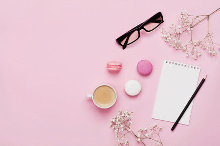 Coffee, cake macaron, clean notebook, eyeglasses and flower on pink table from above. Female working desk. Cozy breakfast. Flat lay style. Stock Photo