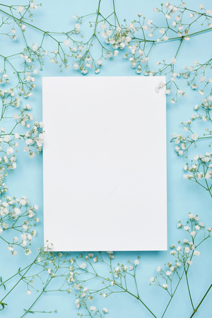 Wedding mockup with white paper list and flowers gypsophila on blue background from above. Beautiful floral pattern. Flat lay style. Foto de archivo