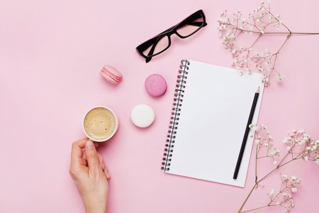 위에서 분홍색 테이블에 커피, 케이크 마카롱, 깨끗한 노트북, 안경 및 꽃의 여자 손 잡고 컵. 여성 책상. 코지 아침 식사. 플랫 평신도 스타일.