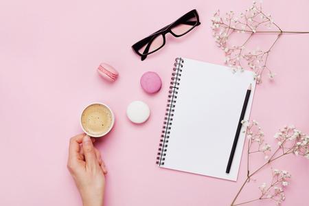 Kvinna hand hålla kopp kaffe, tårta macaron, ren anteckningsbok, glasögon och blomma på rosa bord ovanifrån. Kvinna skrivbord. Mysig frukost. Plattlättestil. Stockfoto