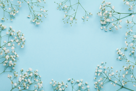 Wedding flower frame on blue background from above. Beautiful floral pattern. Flat lay style.