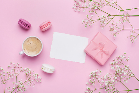 Morning cup of coffee, cake macaron, gift or present box and flower on pink table from above. Beautiful breakfast. Flat lay style. Stockfoto