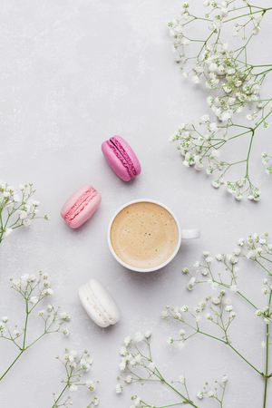 Morning cup of coffee, cake macaron and flower on light background from above. Beautiful breakfast. Flat lay style. Stock Photo