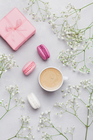 Morning cup of coffee, cake macaron, gift or present box and flower on gray table from above. Beautiful breakfast. Flat lay style. Foto de archivo