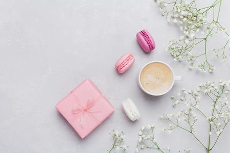 De ochtendkop van koffie, cake macaron, gift of huidige doos en bloem op lichte lijst van hierboven. Prachtig ontbijt. Vlakke lay-stijl.